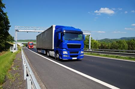 青いトラックが高速道路緑豊かな風景の中に電子通行料のゲートを通過します。赤いトラック、橋および森林に覆われた山を背景に。青い空に白い