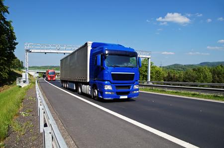 Blue truck passing through the electronic toll gates on the highway in a wooded landscape. Red truck, bridge and forested mountains in the background. White clouds in the blue sky.