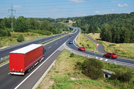 赤いトラックと樹木が茂った国の赤い乗用車のアスファルトの道路。交通標識のスリップ道は、道を譲る。遠くに電子通行料のゲート。上からの眺