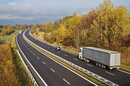 白いトラックとカラフルな秋の風景に赤い乗用車のアスファルトの道路。バック グラウンドで暗い雲の晴れた日。上からの眺め。