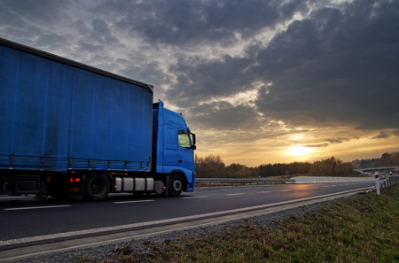 Blue truck on highway at sunset in the countryside. Dark clouds in the sky.