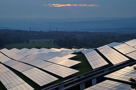 Solar power station at dusk. Industrial landscape with factory chimneys and forested mountains fading into the misty haze in the background. View from above. Standard-Bild
