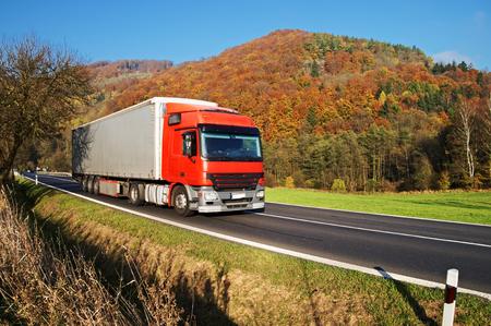 적 열하는 단풍의 숲이 우거진 된 산에서 아스팔트 도로에 빨간색 트럭. 푸른 하늘이 맑은 화창한 날.