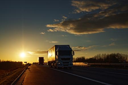 Trucks on asphalt highway in a rural landscape at sunset.