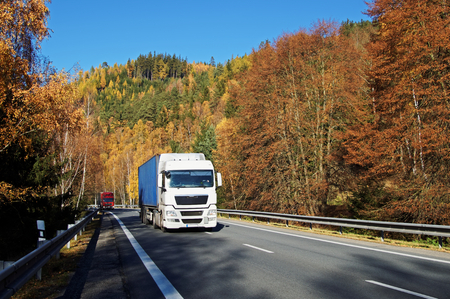 Trucks on asphalt road in a wooded valley below the mountain, blazing with autumn colors. Sunny autumn day with blue sky.