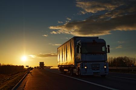 Trucks on asphalt highway in a rural landscape at sunset. Clouds in sunset colors in the blue sky.