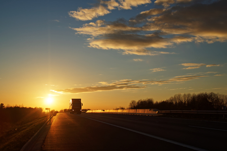 Asphalt road with oncoming truck in a rural landscape at sunset.