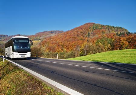 Witte Bus die bij de asfaltweg aankomt door de vallei onder de beboste berg van gloeiende de herfstkleuren. Heldere zonnige dag met blauwe luchten.