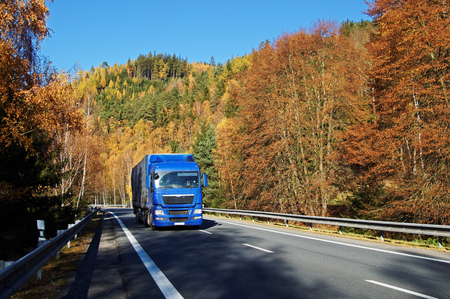 Blue truck on asphalt road in a wooded valley below the mountain, blazing with autumn colors. Sunny autumn day with blue sky.