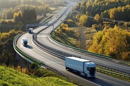 Asfaltweg met elektronische tolpoorten in de herfstbos. Drie vrachtwagens op de weg. De brug over de vallei. Uitzicht van boven. Zonnige dag met heldere herfstkleuren.