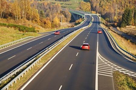 秋の風景の 3 つの赤い乗用車とアスファルトの道路。落葉樹の鮮やかな秋の色。遠くに電子通行料のゲート。秋の晴れた日。上からの眺め。