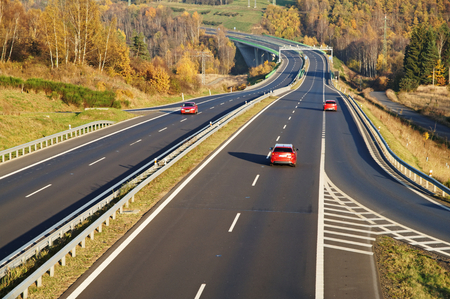 Asphalt highway with three red passenger cars in autumn landscape. Vibrant autumn colors of deciduous trees. Electronic toll gate in the distance. Autumn sunny day. View from above. Standard-Bild