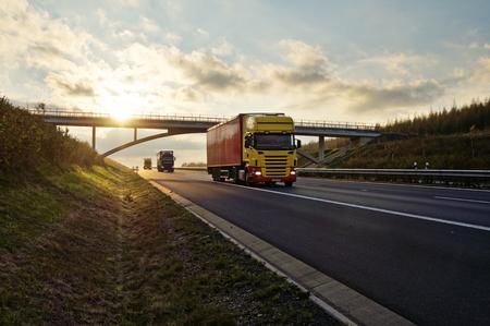 일몰시 아스팔트 도로에 콘크리트 다리 아래를 통과하는 트럭. 스톡 콘텐츠