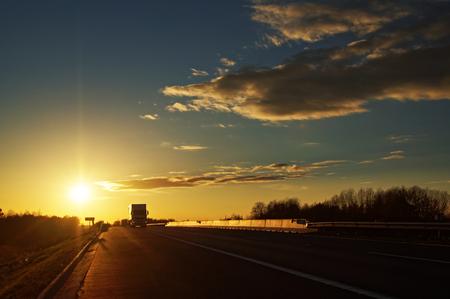 夕暮れ時の農村風景で対向のトラックとアスファルトの道路。