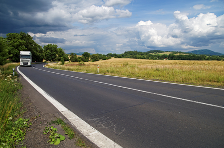 The asphalt road in rural countryside with dramatic clouds in the sky. White truck drive out from the bend between trees in the distance. Cornfield and wooded mountains in the background. Banco de Imagens