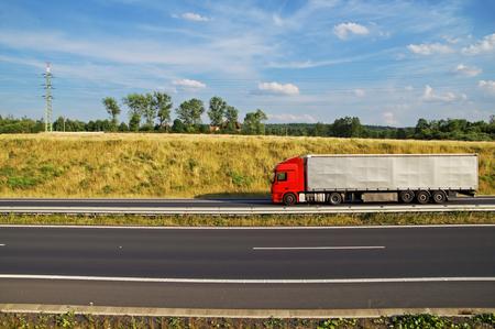 빨간색 트럭 아스팔트 고속도로 잔디 경사 아래에 운전. 수평선에 전기 pylons, 숲과 마을 집. 화창한 여름 날 푸른 하늘과 흰 구름.