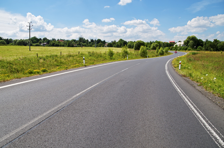 Empty asphalt road with a double bend between flower meadows in the countryside. Red car on the road in the distance. Village among the green leafy trees background. Clear sunny day with blue skies and white clouds.