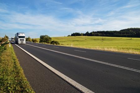 농촌 풍경에 수평선에 상승하는 아스팔트도. 흰색 트럭 멀리에서 도착합니다. 초원 및 백그라운드에서 숲입니다. 푸른 하늘과 흰 구름과 화창한 날입 스톡 콘텐츠