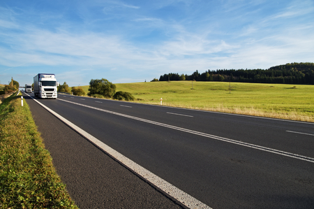Asphalt road rising to the horizon in rural landscape. White trucks arriving from afar. Meadow and forest in the background. Sunny day with blue skies and white clouds.