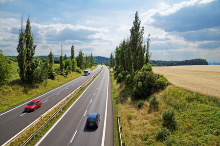 Country landscape with highway leading poplar alley next to a cornfield. Motion blur speeding cars. White truck coming from afar. View from above. Summer sunny day.