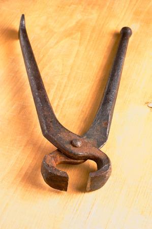 trabajo manual: viejas tenazas trabajo hecho a mano oxidados en tabla de madera dañada ninguna gente Foto de archivo