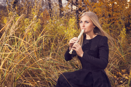 Beautiful young blonde woman playing flute recorder in autumn forest at sunset, opposing windy weather