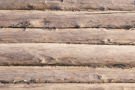 knotty: Textured obsolete wooden wall with cracked surface and tow between logs Stock Photo