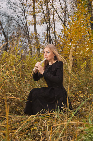 alone person: Beautiful young blonde woman playing flute recorder in autumn forest at sunset, opposing windy weather
