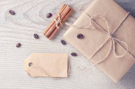 paper board: Rustic gift box with blank tag nearby decorated coffee beans and cinnamon on old white wooden table cold filtered