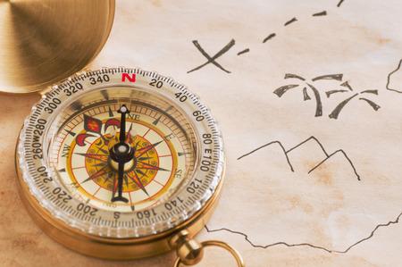 isla del tesoro: Primer plano de la brújula sobre hoja de papel amarillento manchado de parte de dibujado a mano mapa esquemático del tesoro Foto de archivo