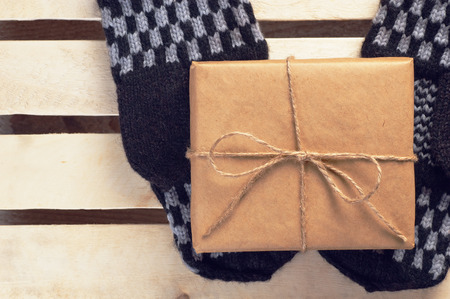grid paper: Christmas gift box packed brown paper and twine on handmade mittens lying on wooden grid panel top view vintage filtered