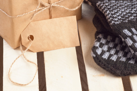 grid paper: Christmas gift box packed brown paper and twine with blank tag and  handmade mittens nearby on wooden grid panel