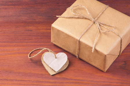 Rustic gift box packed brown paper and twine with two handmade cardboard hearts tied together on wooden table with space for text