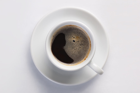 cheerfulness: Cup of hot fresh black coffee with foam against white background viewed from top. Concept of morning, energy and cheerfulness.