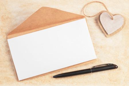 hoja en blanco: sobre de papel marrón, con hoja en blanco decorada dos corazones de cartón hechos a mano atados juntos como colgante y la pluma en el papel viejo con espacio para texto