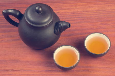 pu: Two clay glazed tea bowls with brewed pu-erh tea and clay teapot on red wooden table vintage filtered with place for text Stock Photo