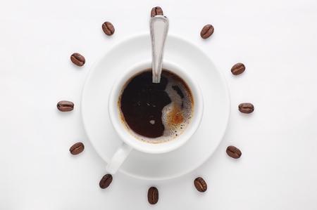 Taza de café con la cuchara en el plato y granos de café contra el fondo blanco formando esfera del reloj visto desde arriba como símbolo de la mañana, la energía y la alegría Foto de archivo