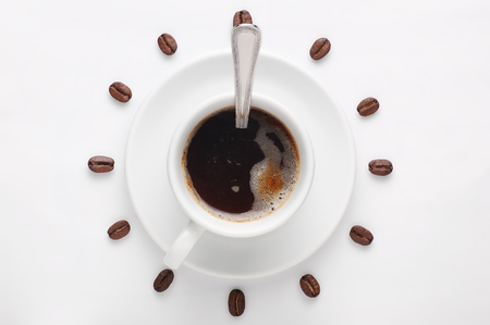 Coffee cup with spoon on saucer and coffee beans against white background forming clock dial viewed from above as symbol of morning, energy and cheerfulness Archivio Fotografico
