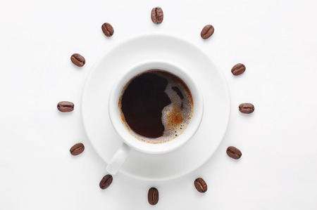 seven o'clock: Cup of strong coffee with foam on saucer and coffee beans against white background forming clock dial viewed from above Stock Photo