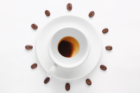 spent: Drunk cup of strong coffee with coffee spent grounds on saucer and coffee beans against white background forming clock dial viewed from above
