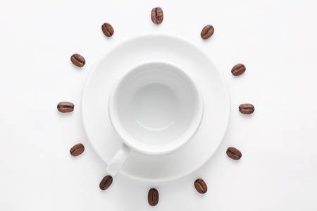 seven o'clock: Empty coffee cup on saucer and coffee beans against white background forming clock dial viewed from above Stock Photo