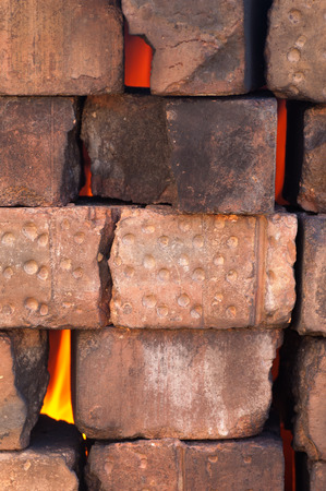 fire bricks: Fire flame behind an old dry masonry wall of burnt bricks, vertical image
