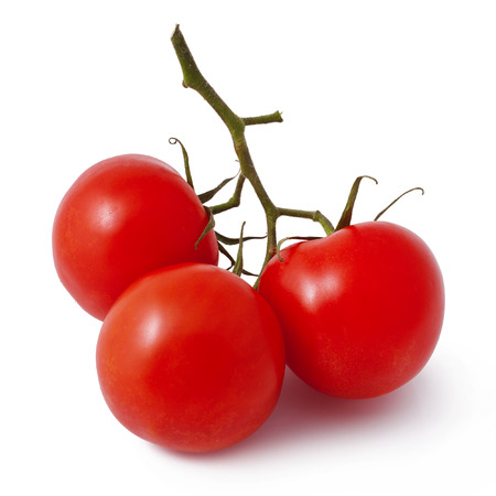 three fresh tomatoes with green leaves isolated on white