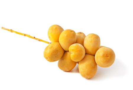 A bunch of yellow raw dates on white background