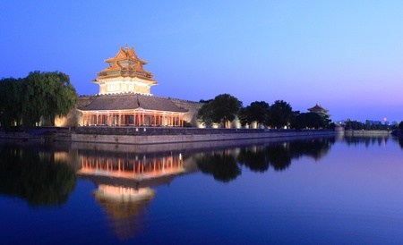 Night scene of Northeast corner of forbidden city,the reflection in the moat, Beijing China. photo