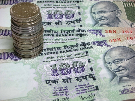 Indian Currency - Three one Hundred Rupee Notes / bills and a coin stack Stock Photo
