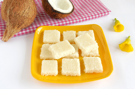 gratings: Coconut burfi, a delcious Indian sweet dish made from coconut gratings and sugar.