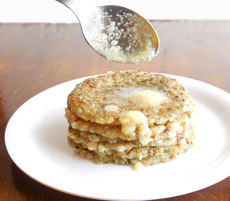Sabudana thalipeeth, or tapioca flat bread, an Indian vegetarian dish with ghee topping, which is eaten typically to break a fast. Stock Photo