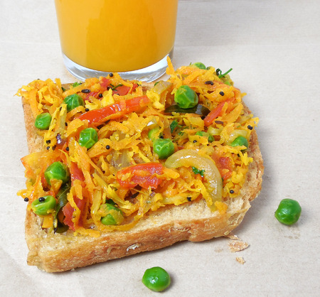 gratings: Indian food masala bread sandwich made from a slice of wheat bread and cooked vegetables like tomato, onion, pea and carrot gratings. Stock Photo