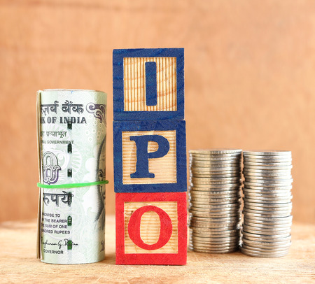 Initial public offering, or IPO, concept, indicated with wooden blocks with letters forming the word IPO and Indian rupees and stack of coins.